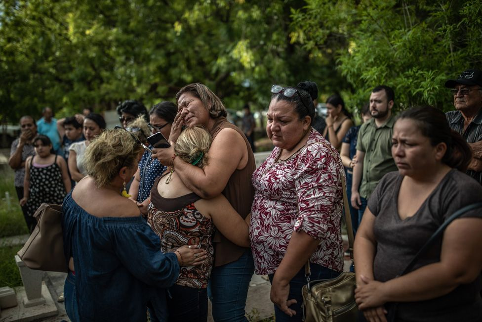Mirna Nereyda hugs a mother who found the remains of her son four months after he went missing