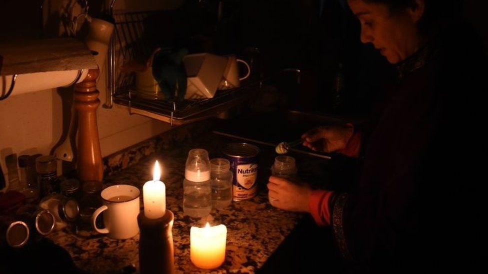 A woman works by candle in her kitchen during a blackout in Uruguay