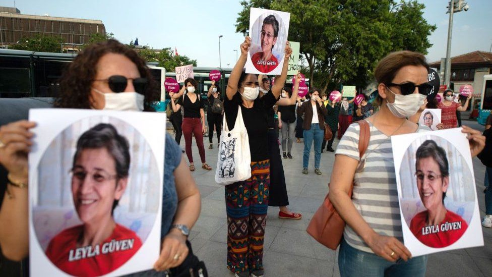 Demonstrators hold pictures of HDP lawmaker Leyla Guven