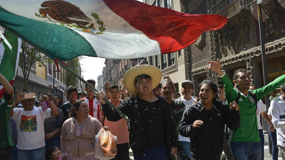 A South Korean man waves the Mexican flag in Zocalo square, Mexico City