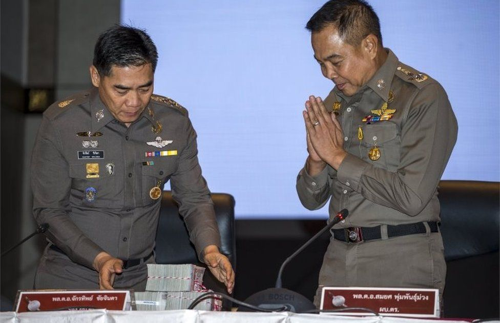 Thai national police chief Somyot Poompanmuang (R) gestures as he hands over a reward to deputy police chief Chakthip Chaijinda before a news conference about the Bangkok blast which killed 20 people, including foreigners, at the Royal Thai Police headquarters in central Bangkok, Thailand, September 28, 2015.