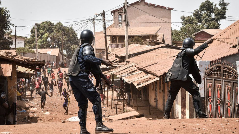 A policemen taking on protesters in neighbourhood of Conakry, Guinea - 27 February 2020