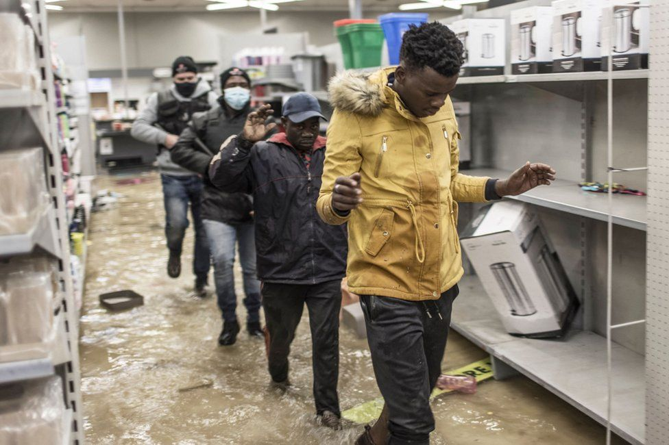 Suspected looters who surrendered to armed private security officers are marched outside, in a flooded mall in Vosloorus, on 13 July 2021