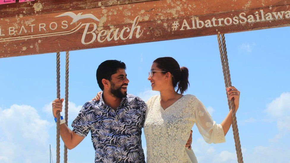 The couple posing by a sign in Mexico