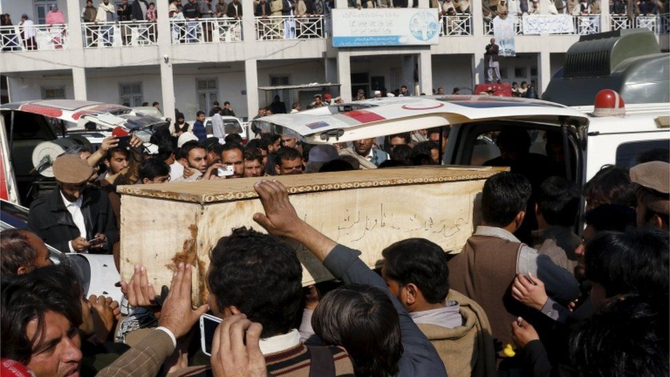 Mourners surround a coffin