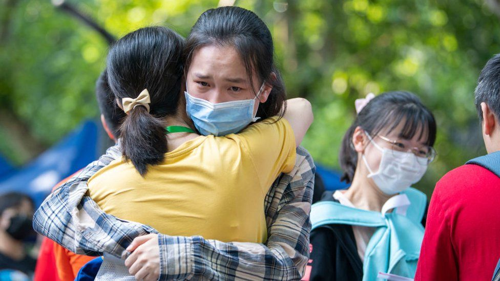 A student hugs her teacher before entering an exam site during the 2020 National College Entrance Exam