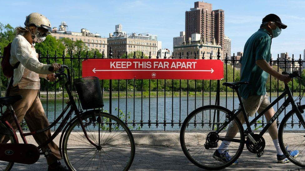 """People wearing protective masks walk their bicycles past a social distancing sign reading """"KEEP THIS FAR APART"""" at Jacqueline Kennedy Onassis Reservoir in Central Park during the coronavirus pandemic on May 17, 2020 in New York City"""