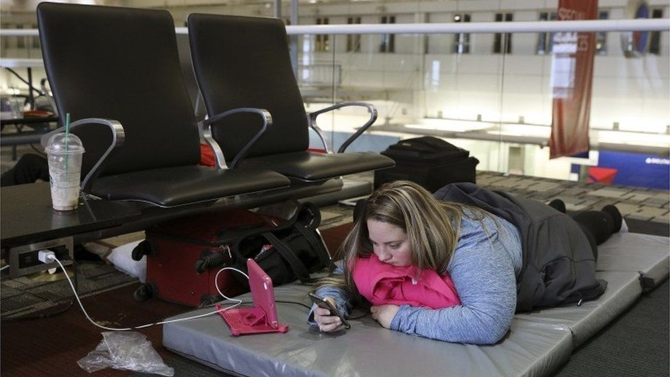 Chelsey Kalmback, 29, plays on her phone while waiting for a rescheduled flight to North Dakota after several flights were delayed or cancelled mostly due to weather, Monday, Dec. 26, 2016, at Minneapolis-Saint Paul International Airport, in Minnesota