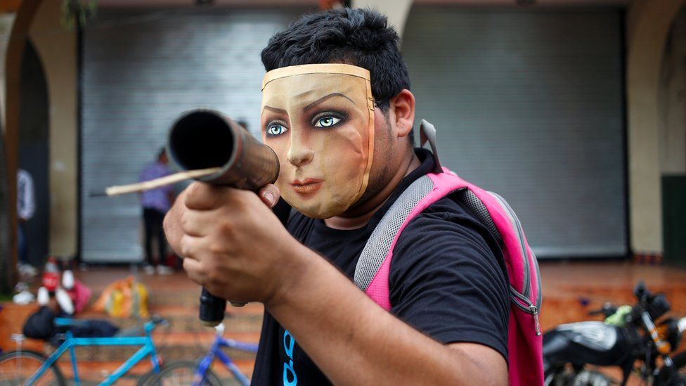 A demonstrator poses for a photo with his homemade mortar pointed directly at the camera, face covered by a cloth mask of a woman's face