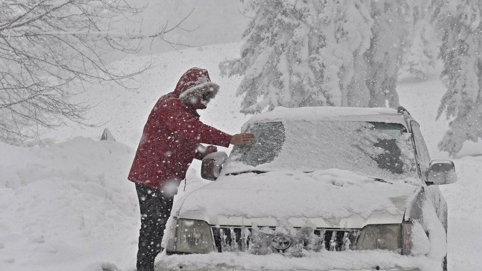 """A person clears snow from a vehicle after a heavy snowfall in Casaglia, Mugello, Florence""""s province, Italy"""