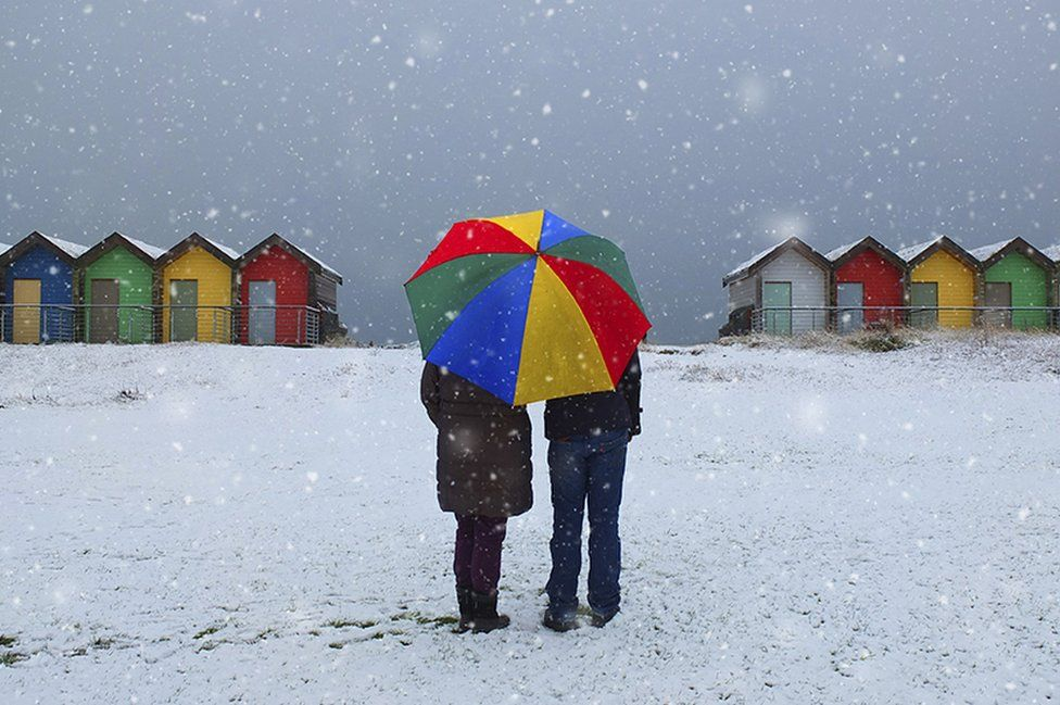 A couple holding an umbrella standing in snow with beach huts in the background
