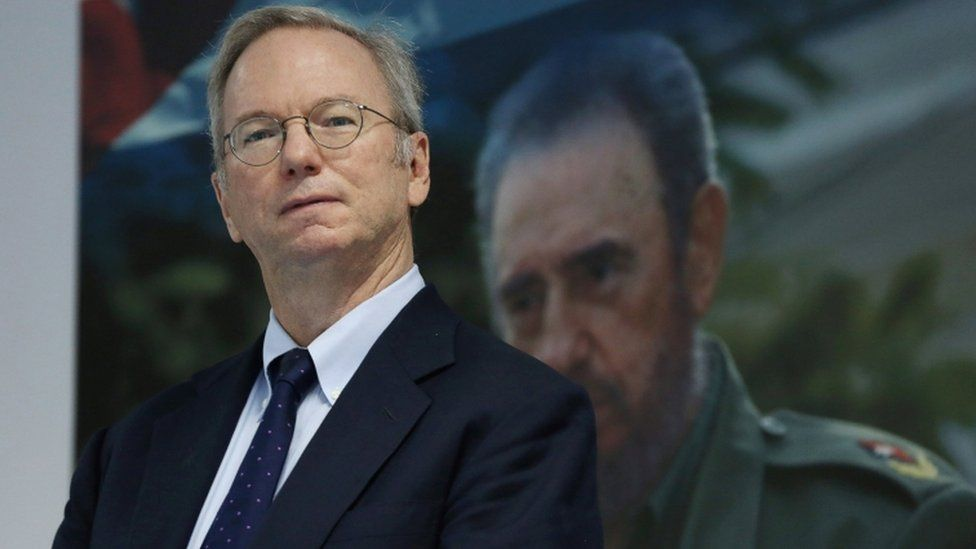Eric Schmidt, chairman of Alphabet Inc. stands in front of a picture of former Cuba's President Fidel Castro before signing documents in Havana