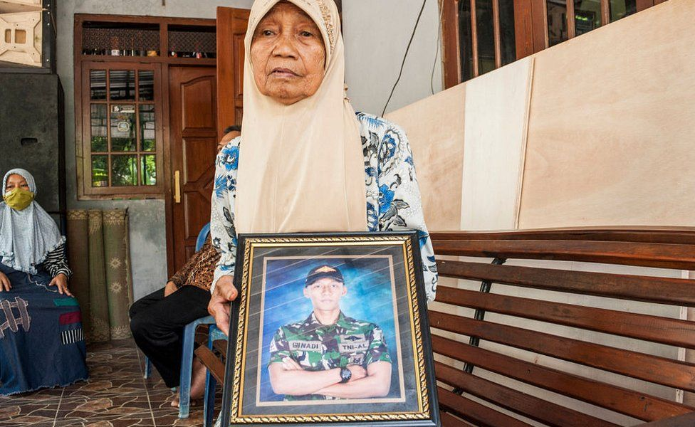 Sarikem holds a photo of her grandson Gunadi Fajar Rahmanto at their home in Yogyakarta on April 26, 2021