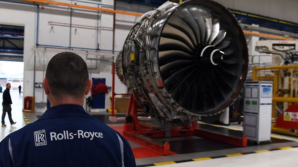 Rolls-Royce worker stands in front of a jet engine