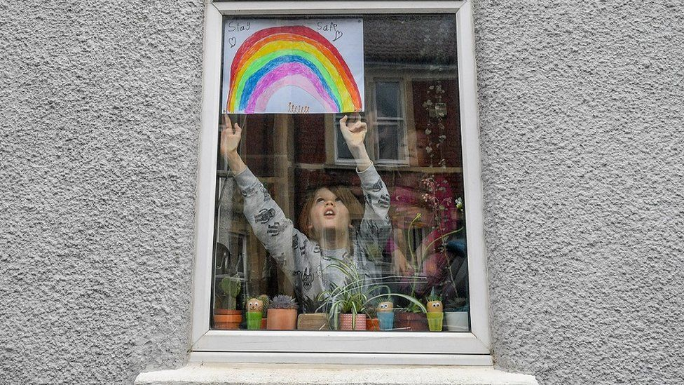 Child putting rainbow picture in window