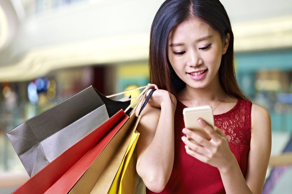 Young woman using phone while shopping