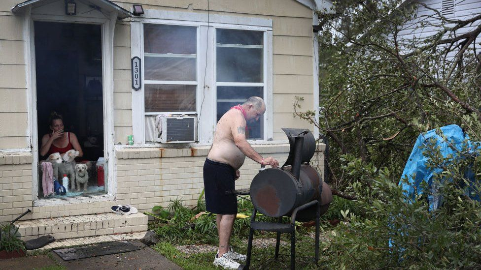 David Veillon cooks food that was left in his refrigerator before it goes bad after Hurricane Laura passed through the area on August 28, 2020 in Lake Charles, Louisiana