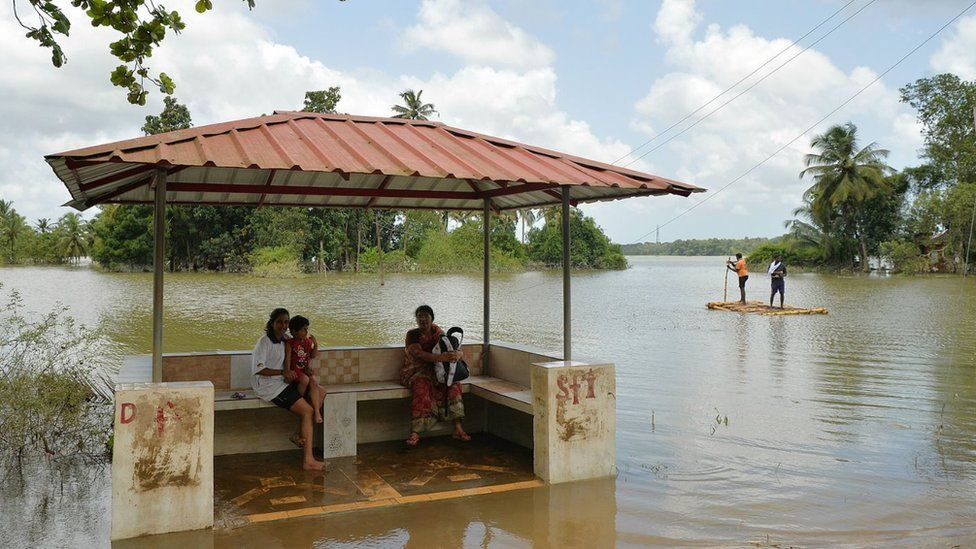 Women at a flooded bus stop