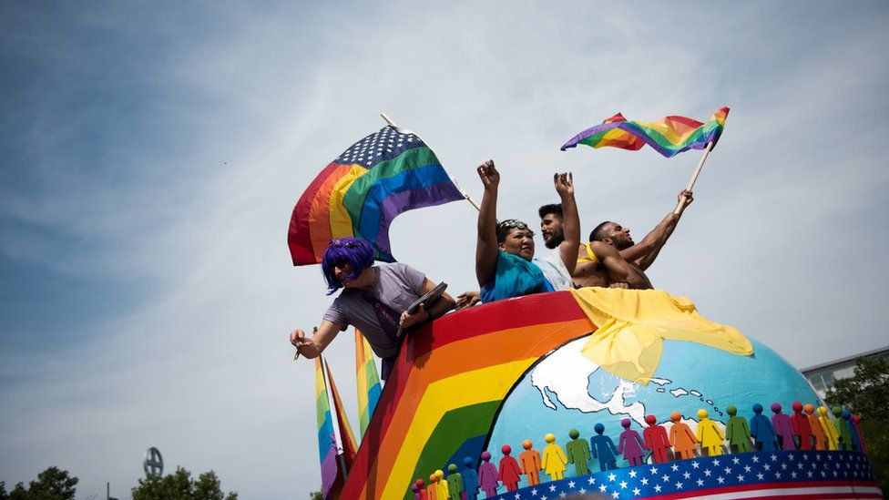 People dance during the annual Gay Pride parade in Berlin in July this year