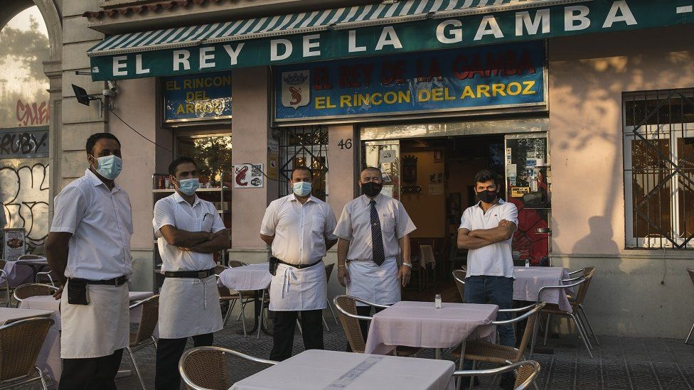 The staff of El Rey de la Gamba 2 restaurant poses for photos outside their restaurant on July 27, 2020 in Barcelona, Spain