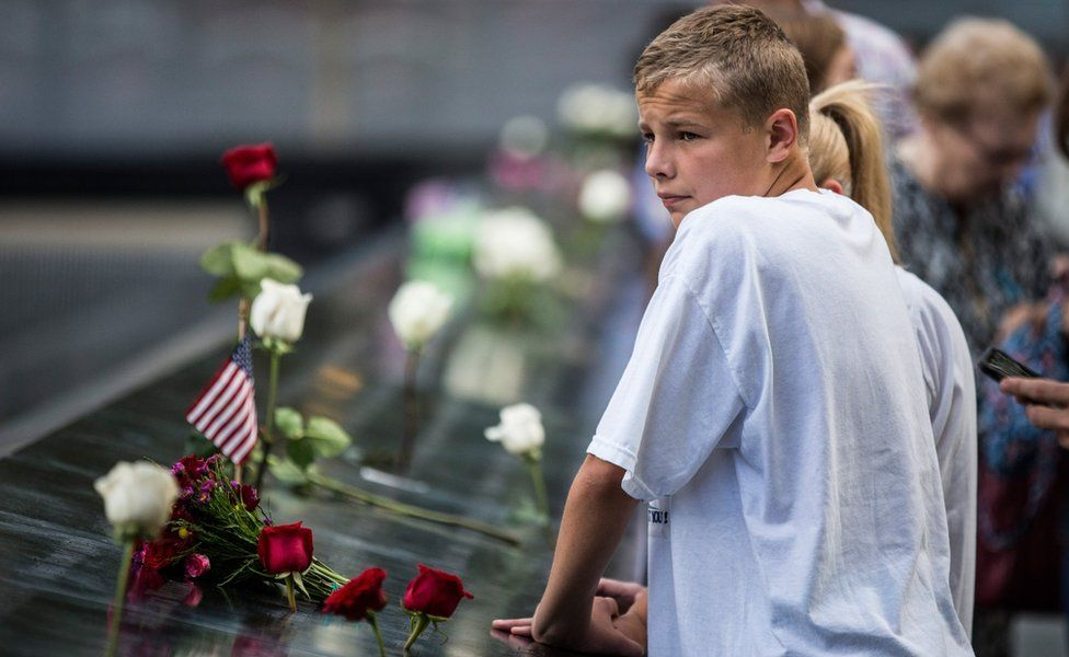 A boy stands near the memorial in New York