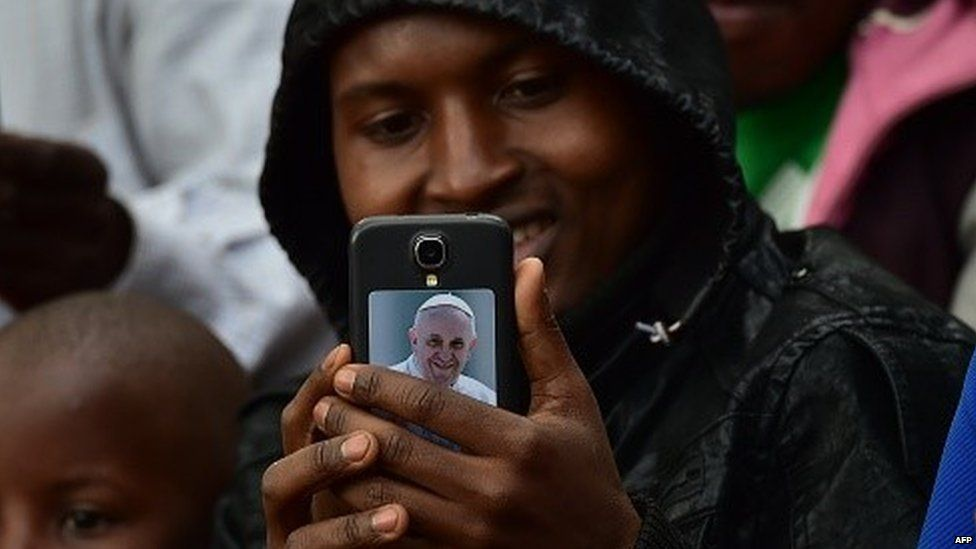 A believer holds a smartphone displaying a picture of Pope Francis as people wait for the arrival of the pope for an open mass at Namugongo Martyrs' Shrine in Namugongo, Uganda, November 28, 2015.