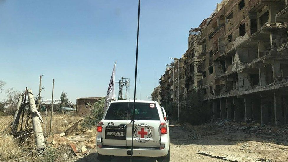 Image by Syrian Red Cross showing aid convoy passing badly-damaged buildings in Darayaa, Syria - 1 June 2016