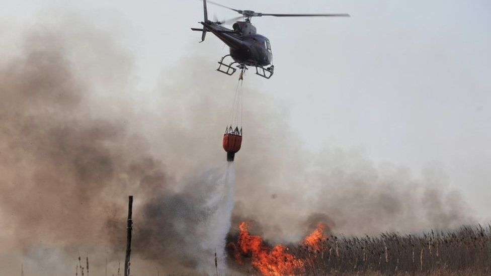 Helicopter drops water on fires in Poland