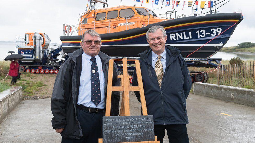 Pwllheli RNLI Chair Alan Jones and Charles Denton, Godson and executor of the Richard Colton Estate unveiling a plaque to officially open Pwllheli's new RNLI boathouse