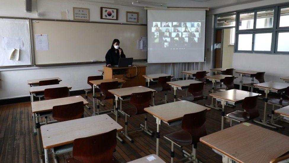 Teacher in empty classroom giving online class to pupils via video link