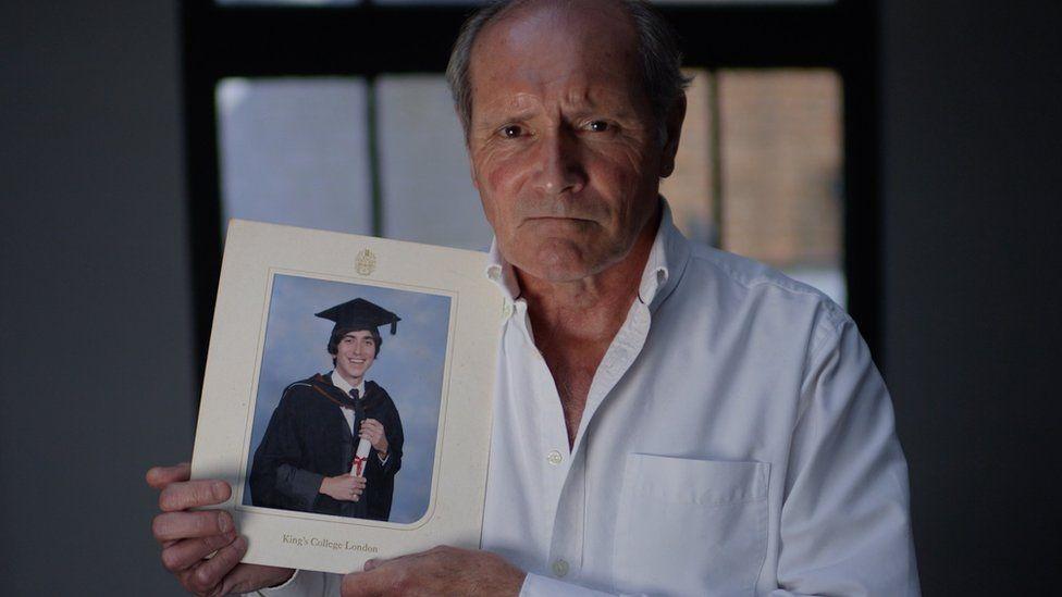 Derek Jones holding photo of son