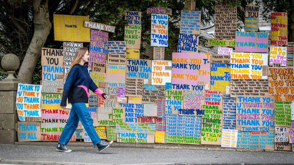 woman walking past thank you nhs signs