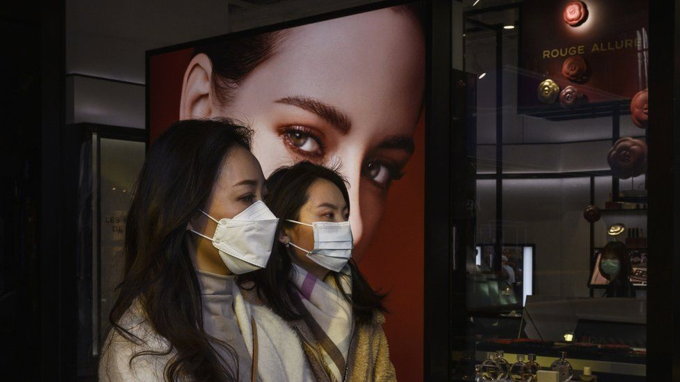 Women wearing masks in a Chinese shopping centre walk past a billboard of a white woman