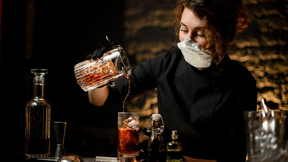 A bartender pouring a drink, wearing a mask