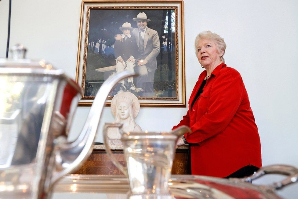 Diane Capone, granddaughter of American gangster Al Capone, stands next to a painting of her grandfather and father, Sonny Capone, from the 1920s before the auction on 5 October 2021