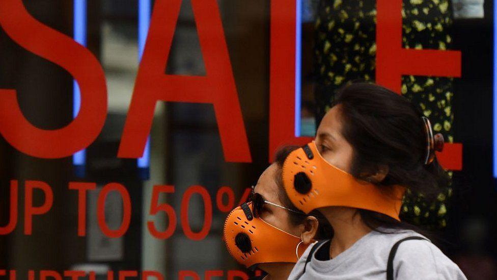 Women in masks outside shop