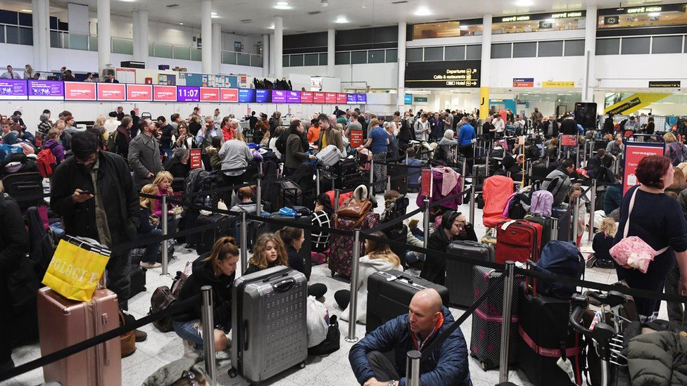 Crowds of people waiting at Gatwick Airport