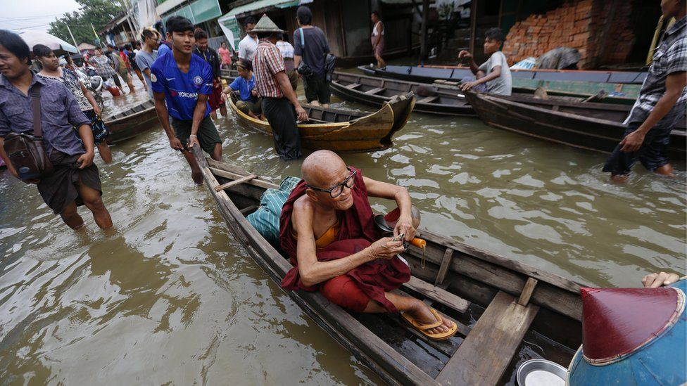 Buddhist monk sits on the boat as people use boat to pass through flooded road