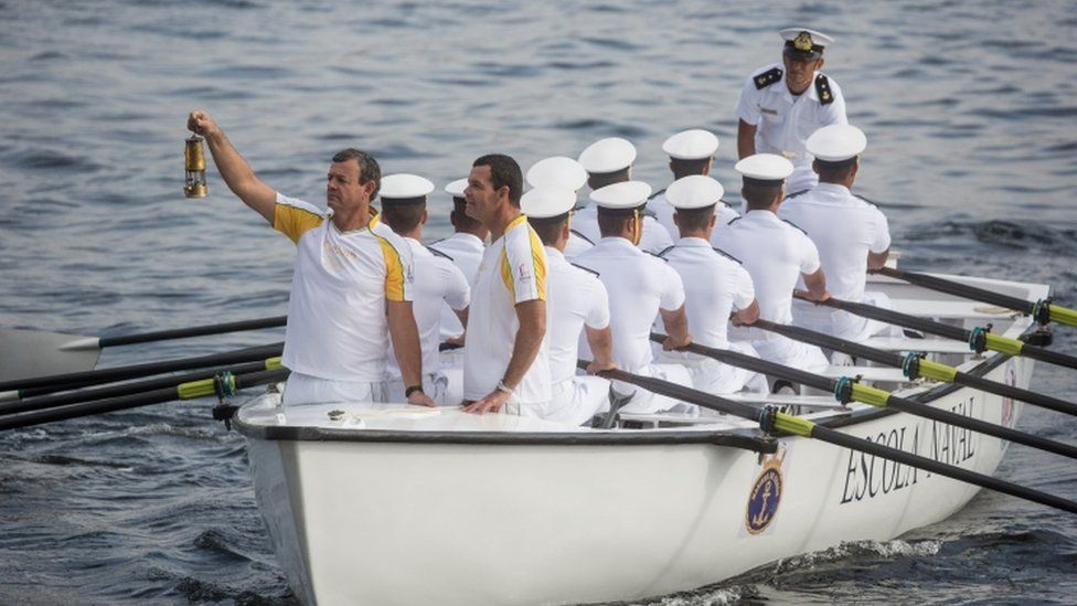 Olympian Lars Grael (L) carries the Olympic flame aboard a Brazilian Naval Academy boat during the Olympic Torch relay ahead of the Rio 2016 Olympic Games on August 3, 2016 in Rio de Janeiro, Brazil.