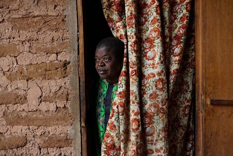 Man looking through a curtain