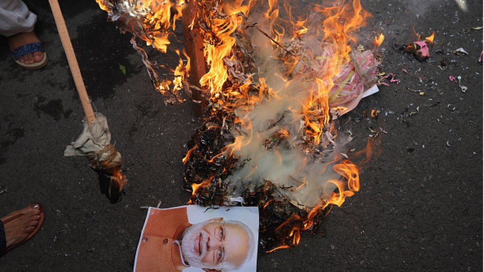 Members of the Congress women's wing burn the effigy of PM Narendra Modi to burn during a protest against alleged rape, murder and forceful cremation of a 9 year old girl, in Delhi.
