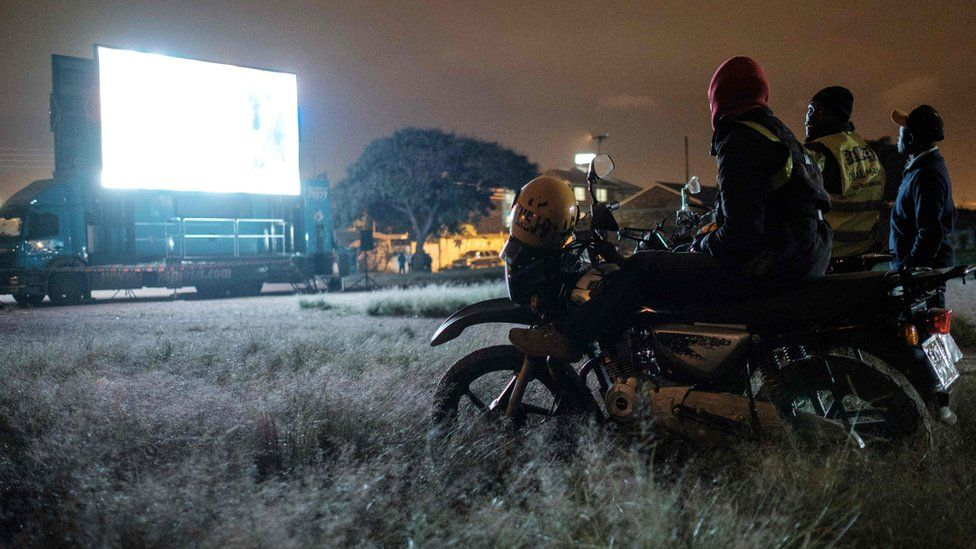 Kenyans on bikes watch a football match on a giant screen in Nairobi - Tuesday 26 June 2018