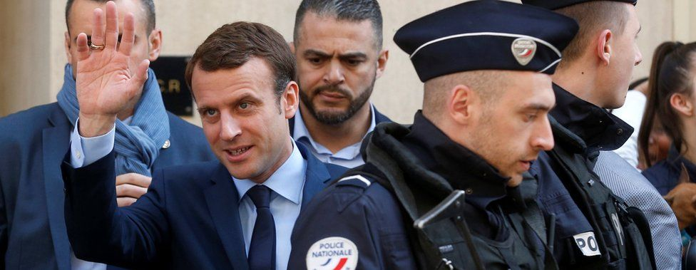 Emmanuel Macron waves to supporters on 24 April
