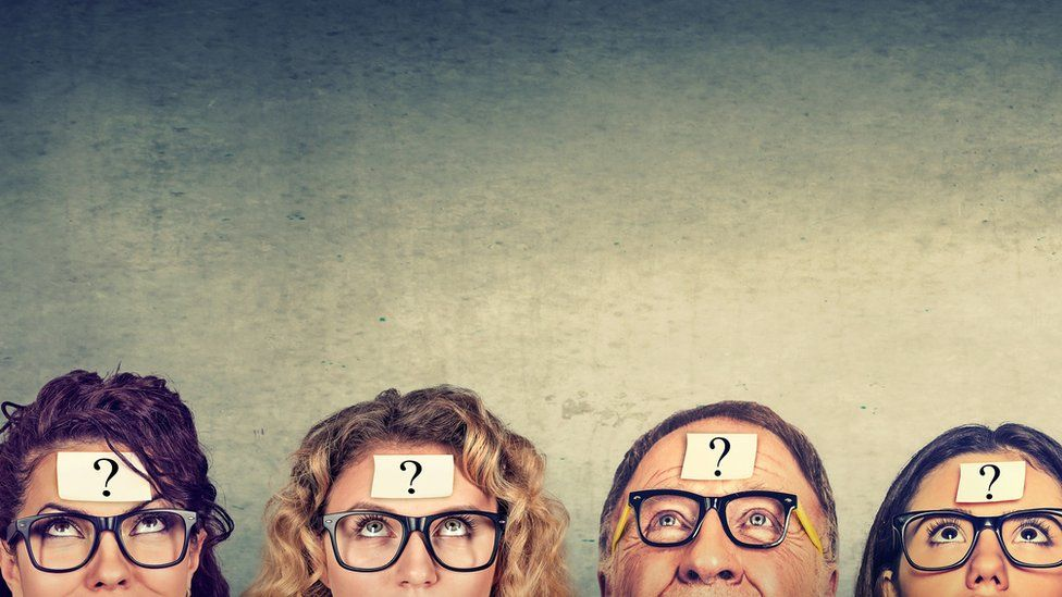 Stock photo of people thinking with question mark signs on their foreheads