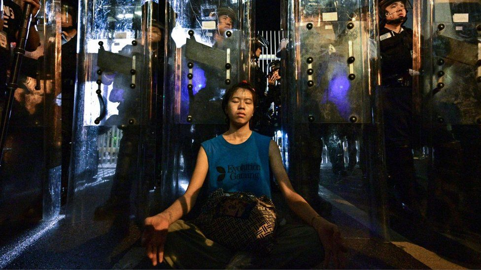 A female protester meditates in front of riot police outside the government headquarters in Hong Kong