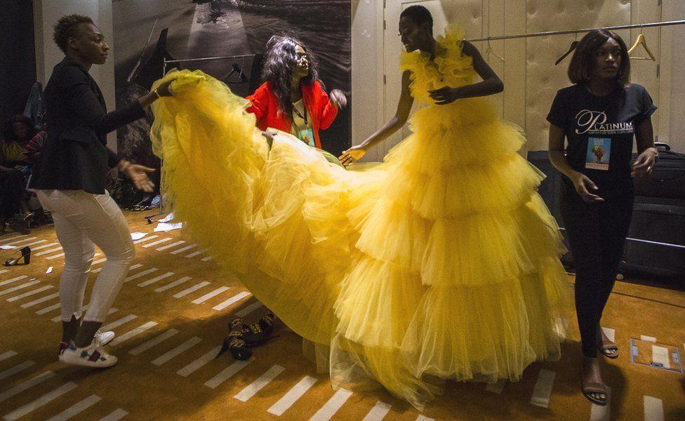 Des créateurs de mode, stylistes et assistantes aident une mannequin avec sa robe dans les coulisses de la Semaine de la mode de Dakar à Dakar, Sénégal