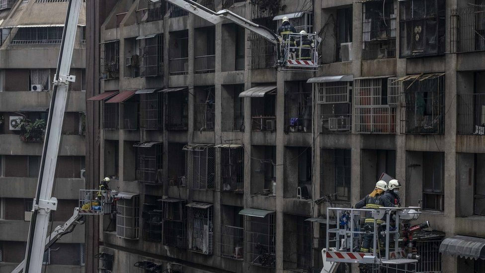 Firefighters search for victims from a residential building in the wake of a fire on 14 October 2021, in Kaohsiung, Taiwan
