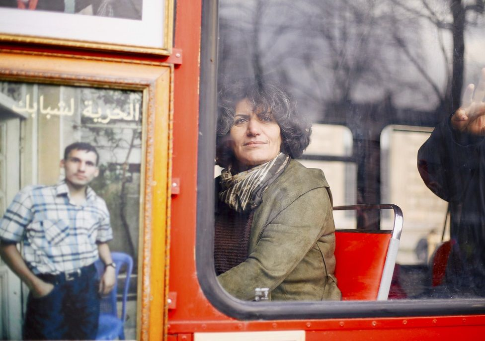 A Syrian refugee looks out of a bus a window