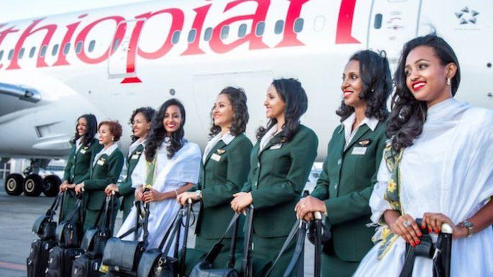 Female cabin crew on tarmac next to plane