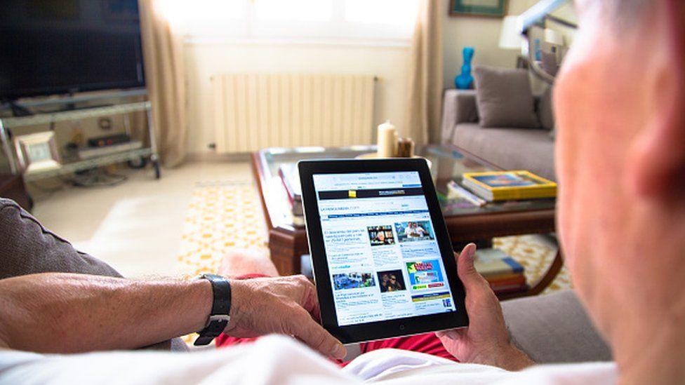A man reading the news on an iPad